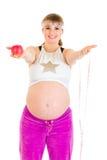 Cinta y manzana de la medida de la explotación agrícola de la mujer embarazada Fotografía de archivo