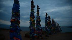 Cintas coloridas en polos de madera en el lago Baikal en Siberia metrajes