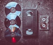 Cintas de video de la endecha del plano, CD' s, casete audio en un concre negro imagen de archivo