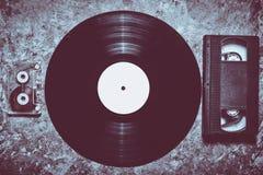 Cintas del disco de vinilo, audios y de video en un hormigón gris fotografía de archivo libre de regalías