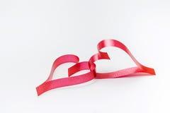Cintas formadas como corazones en el fondo blanco Foto de archivo