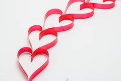 Cintas formadas como corazones en el fondo blanco Foto de archivo libre de regalías