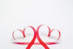 Cintas formadas como corazones en el fondo blanco Imágenes de archivo libres de regalías
