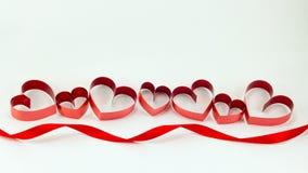 Cintas formadas como corazones en el fondo blanco, día de San Valentín concentrado Foto de archivo