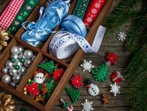 Cintas, gotas, juguetes, artes de la Navidad en una caja de madera Fotografía de archivo