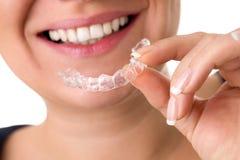 Cintas invisíveis de sorriso dos dentes da terra arrendada fêmea Fotografia de Stock