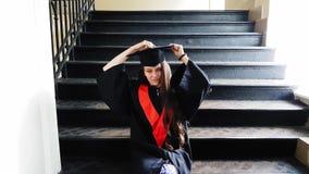 Cintas maestras graduadas del estudiante hermoso su pierna con un yeso mientras que se sienta en pasos del metal en la universida almacen de metraje de vídeo