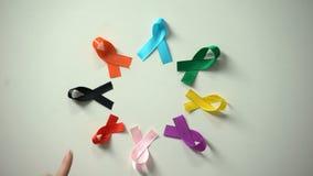 Cintas multicoloras de colocación femeninas en campaña del día de la conciencia del cáncer del mundo de la tabla almacen de metraje de vídeo