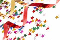 Cintas rojas y de oro y pequeño confeti coloridos Imágenes de archivo libres de regalías