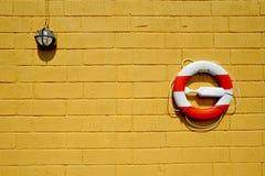 Cinto de salvação na parede amarela foto de stock royalty free