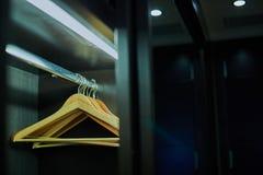 Cintre d'habillement sur la table en bois brune Images libres de droits