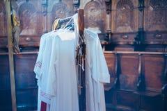 cintres avec des vêtements des enfants de choeur et des croix en bois, dans le ch images libres de droits