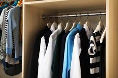 Cintres avec les vêtements adolescents sur le support dans la garde-robe image stock