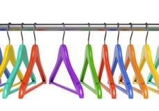 Cintres colorés sur le rail de tissu Photos libres de droits