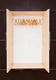 Cintres de manteau en bois sur le rail de vêtements dans le cabinet Image libre de droits