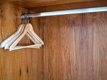 Cintres en bois accrochant sur la barre d'acier inoxydable dans le placard en bois de v?tements photo stock