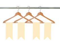 Cintres en bois avec des étiquettes (labels) d'isolement sur le blanc Image libre de droits