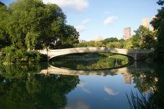 Cintrez le pont et les arbres au lac au Central Park avec le ciel Photographie stock libre de droits