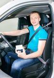 Cinturón de seguridad de la cerradura del muchacho y carné de conducir adolescentes de la demostración Fotografía de archivo libre de regalías
