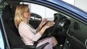 Cinturón de seguridad maduro de la cerradura de la mujer que se sienta en un nuevo coche en la representación almacen de video