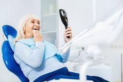 Cintura acima da mulher deleitada no escritório dental foto de stock royalty free