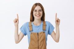 Cintura-acima disparada da mulher encantador despreocupada deleitada com o sorriso amigável que levanta as mãos que aponta acima  fotografia de stock royalty free
