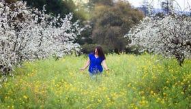 A cintura acima do retrato da jovem mulher na parte superior azul brilhante no pomar de florescência e a mostarda amarela colocam Fotos de Stock