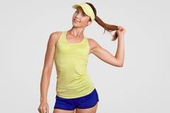 A cintura acima do tiro do jogador de tênis saudável bonito auto-confiante guarda a cauda de pônei, vestida no sportswear, poses  fotos de stock