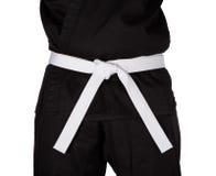 Cintura bianca di karatè legata intorno all'uniforme del nero del torso Fotografie Stock