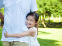 Cintura bonita del padre del abrazo de la niña en el parque Foto de archivo libre de regalías