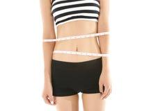 A cintura da mulher com uma fita métrica isolada no fundo branco imagem de stock