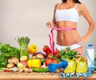 Cintura de la mujer con la cinta métrica sobre fondo de la comida Imagenes de archivo