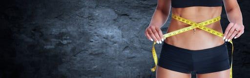 Cintura de la mujer con la cinta métrica sobre fondo gris Fotografía de archivo libre de regalías