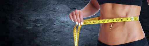 Cintura de la mujer con la cinta métrica sobre fondo gris Fotos de archivo