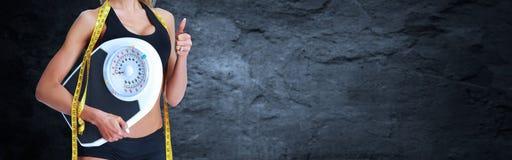 Cintura de la mujer con la cinta métrica sobre fondo gris Foto de archivo libre de regalías