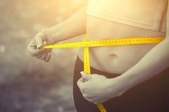 Cintura de medición de la muchacha del deporte con la cinta métrica amarilla Reducción del exceso de peso Fotografía de archivo