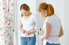 Cintura de medición de la mujer delante del espejo Fotos de archivo libres de regalías
