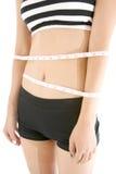Cintura de medición de la mujer delgada con la cinta de la medida aislada en el fondo blanco Fotografía de archivo libre de regalías