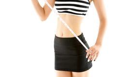 Cintura de medición de la mujer delgada con la cinta de la medida aislada en el fondo blanco Fotos de archivo
