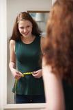 Cintura de medición del adolescente en espejo Fotos de archivo