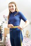 Cintura de medición del adolescente feliz en dormitorio Fotos de archivo