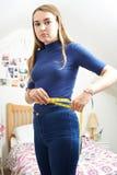 Cintura de medición del adolescente infeliz en dormitorio Fotografía de archivo