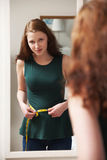 Cintura de medición del adolescente infeliz en espejo Imágenes de archivo libres de regalías