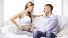 Cintura de medición del marido feliz de la esposa embarazada almacen de video
