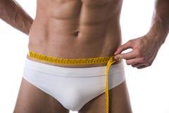 Cintura de medición descamisada muscular del hombre joven con cinta métrica Foto de archivo