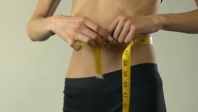 Cintura de medición de la muchacha anoréxica con la cinta-línea y mostrar muy bien, inseguridades metrajes