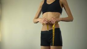 Cintura de medición de la muchacha delgada con la cinta-línea, mostrando muy bien, anorexia como enfermedad mental almacen de metraje de vídeo
