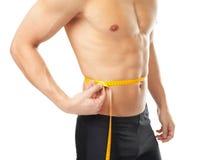 Cintura de medición muscular del hombre joven Imágenes de archivo libres de regalías