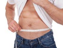 Cintura de medición del hombre muscular Fotografía de archivo libre de regalías