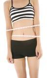 Cintura delgada de la mujer de la dieta con una cinta métrica aislada en el fondo blanco Imagen de archivo